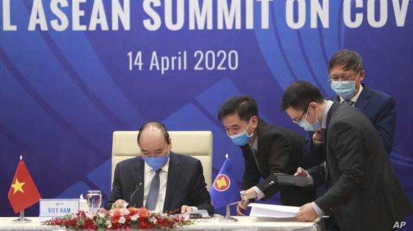 Thủ tướng Nguyễn Xuân Phúc (trái) và các cán bộ chuẩn bị tài liệu trước Hội nghị thượng đỉnh ASEAN đặc biệt về COVID-19 tại Hà Nội, ngày 14.4.2020. Nguồn ảnh: AP.