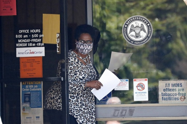 Nhân viên tại trung tâm việc làm ở Pearl, bang Mississippi, với đơn đăng ký nhận trợ cấp thất nghiệp trên tay. Ảnh: AP