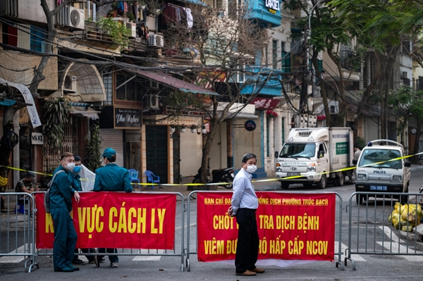 Security and local residents wait at a checkpoint within the quarantined area in Hanoi on March 9. Photographer: Linh Pham/Getty Images
