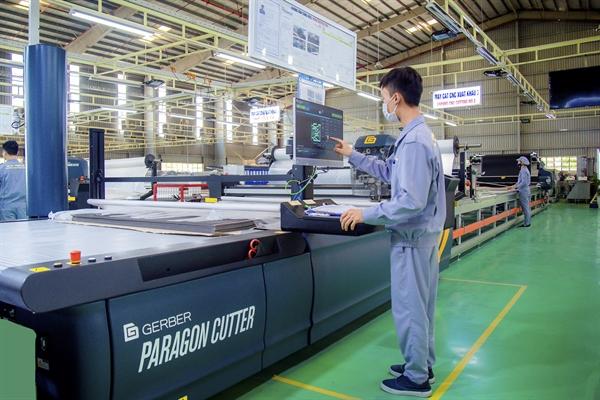 Công nhân điều khiển máy cắt vải CNC tại nhà máy Ghế ô tô.
