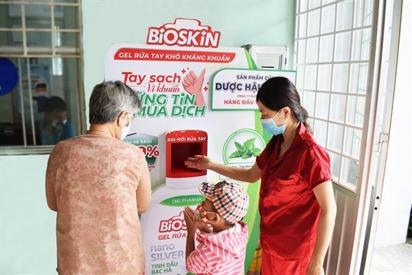 Người dân thành phố Cần Thơ sử dụng máy rửa tay kháng khuẩn tự động và gel rửa tay kháng khuẩn Bioskin do Dược Hậu Giang tài trợ.