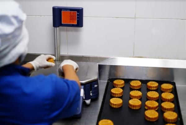 Kiểm tra thủ công kỹ lưỡng từng chiếc bánh trước khi đóng gói.