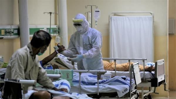 Một nhân viên y tế điều trị cho một bệnh nhân trong phòng cách ly vì COVID-19 tại Bệnh viện Persahabatan ở Jakarta. Bệnh viện sẽ quản lý những liều remdesivir đầu tiên của đất nước Indonesia. Nguồn ảnh: Reuters.