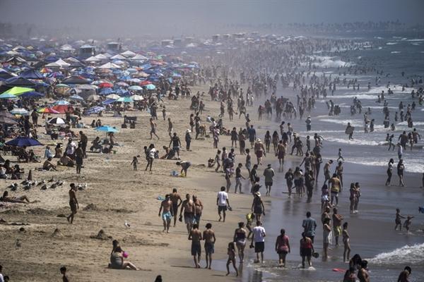 Mọi người tụ tập trên bãi biển ở Huntington Beach, California, khi tiểu bang này nóng lên. Nguồn ảnh: AP.