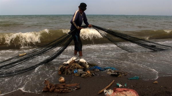 Một ngư dân ở Indonesia tìm kiếm lưới đánh bắt của mình trên một bãi biển đầy rác thải nhựa. Các thiết bị đánh bắt bị bỏ đi đã trở thành mối đe dọa nghiêm trọng đối với môi trường. Nguồn ảnh: Nikkei Asian Review.