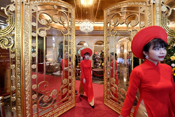 Staff wait to welcome guests in the lobby of the newly-inaugurated Dolce Hanoi Golden Lake hotel, the world's first gold-plated hotel, in Hanoi on July 2, 2020. | CREDIT: MANAN VATSYAYANA/AFP VIA GETTY IMAGES