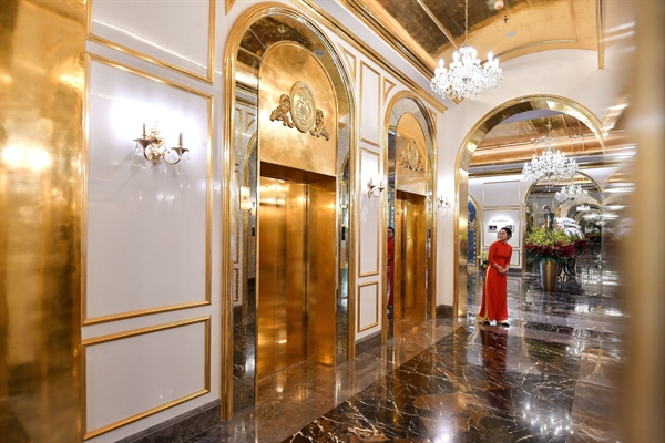 A staff member stands near the lifts in the lobby of the newly-inaugurated Dolce Hanoi Golden Lake hotel, the world's first gold-plated hotel, in Hanoi on July 2, 2020.CREDIT: MANAN VATSYAYANA/AFP VIA GETTY IMAGES