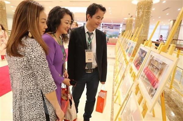Kiều bào tham quan trưng bày ảnh về hoạt đồng của người Việt Nam ở nước ngoài. Ảnh: TTXVN.
