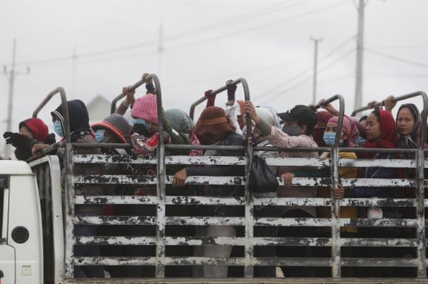 Công nhân may mặc Campuchia về nhà sau ca làm việc. Các cuộc phỏng vấn với gần 400 công nhân ở 9 quốc gia cho thấy mức lương trung bình giảm 21% kể từ khi bắt đầu đại dịch. Ảnh: AP.