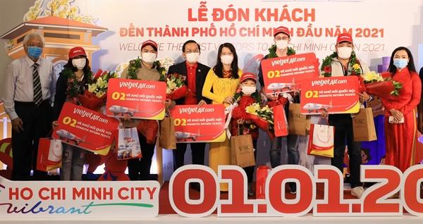 Phó Tổng giám đốc Vietjet Đỗ Xuân Quang (thứ 3 từ trái qua), Giám đốc Sở Du lịch TP.HCM Nguyễn Thị Ánh Hoa (thứ 4 từ trái qua) và cơ quan ban ngành liên quan trao hoa và tặng món quà giá trị và ý nghĩa cho hành khách may mắn.