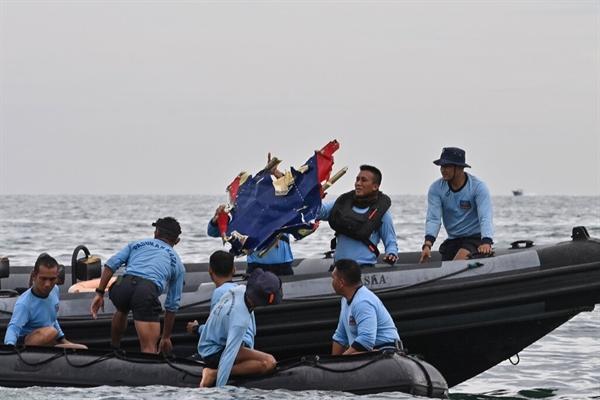 Các thủy thủ đoàn Hải quân Indonesia tìm thấy một mảnh vỡ được cho là từ máy bay Sriwijaya Air. Ảnh: AFP.