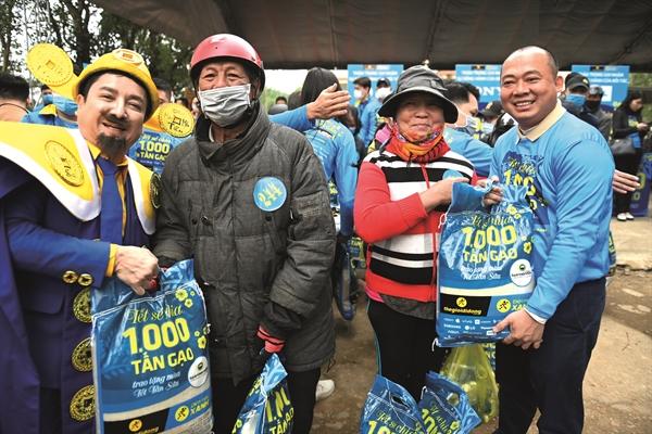CEO Thế Giới Di Động Đoàn Văn Hiểu Em và Thần Tài Xanh, nghệ sĩ Chí Trung trao gạo cho người dân tại lễ khởi động chương trình.