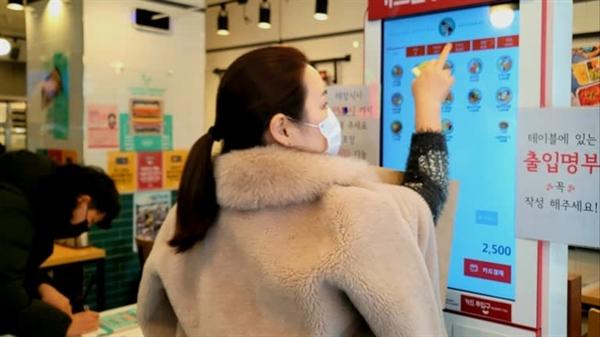 Một phụ nữ chọn đồ từ máy bán hàng tự động tại một quán ăn nhanh ở Seoul: Tự động hóa ngày càng tăng trong ngành dịch vụ thực phẩm đang đè nặng lên việc làm. Ảnh: Nikkei Asian Review.
