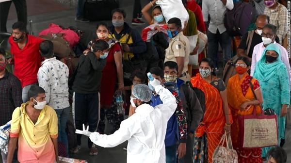 Một nhân viên y tế kiểm tra thân nhiệt khi hành khách đến ga cuối đường sắt ở Mumbai vào ngày 6.1.2021., Giám đốc điều hành Adar Poonawalla của Viện Huyết thanh Ấn Độ cho biết: Ấn Độ không thể đạt được khả năng miễn dịch cộng đồng trong nhiều năm. Ảnh: CNN.