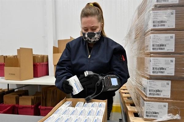 Một công nhân quét mã hộp vaccine COVID-19 Johnson & Johnson. Ảnh: AP.