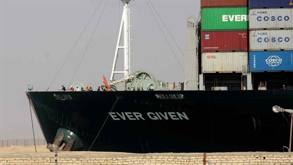 """Tàu Ever Given, một trong những tàu container lớn nhất thế giới, """"mắc cạn"""" đi qua kênh đào Suez vào ngày 29.3. Ảnh: Reuters."""