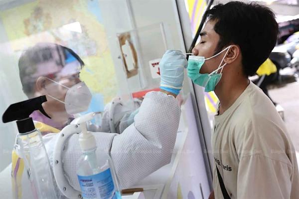 Một nhân viên y tế thu thập tăm bông để xét nghiệm từ một người đàn ông ở quận Klong Toey, Bangkok. Ảnh: Bangkok Post.