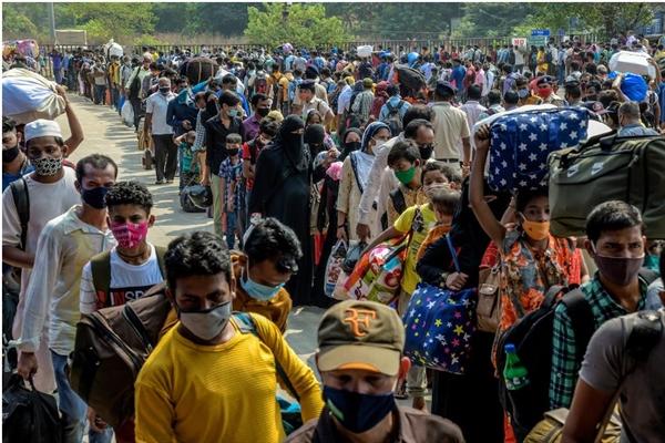 Những người lao động nhập cư chờ đợi bên ngoài Lokmanya Tilak Terminus ở Mumbai, Ấn Độ, để về quê giữa đại dịch. Ảnh: The New York Times.