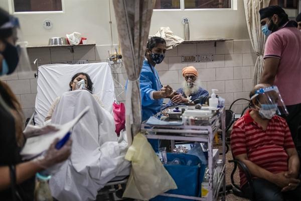 Các nhân viên y tế chăm sóc bệnh nhân COVID-19 trong khu cấp cứu tại một bệnh viện ở New Delhi. Ảnh: The New York Times.