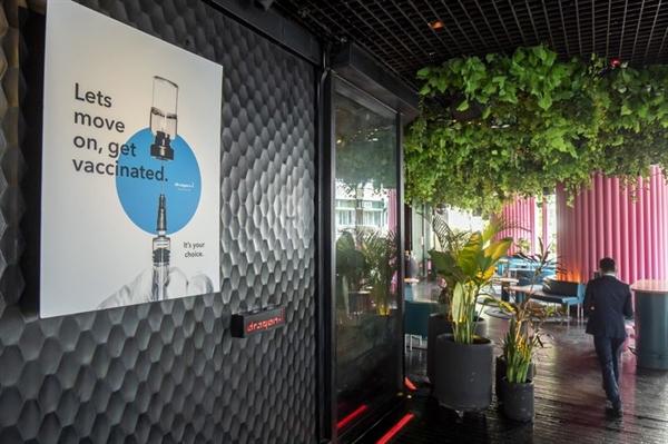 Một tấm áp phích khuyến khích mọi người đi tiêm phòng tại một hộp đêm ở khu giải trí về đêm Lan Kwai Fong hôm 29.4. Ảnh: Bloomberg.