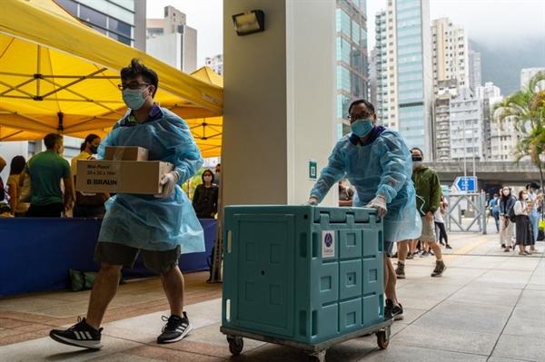 Các nhân viên vận chuyển vật tư y tế đến trung tâm tiêm chủng cộng đồng vào ngày 5.4. Ảnh: Bloomberg.