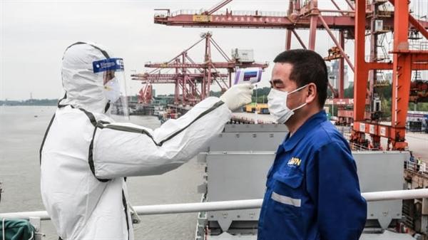 Các biện pháp nghiêm ngặt: Đo nhiệt độ thuyền viên tại một cảng ở Vũ Hán, Trung Quốc. Ảnh: AP.