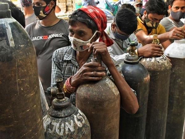Người dân xếp hàng để nạp đầy bình oxy cho những người bị nhiễm COVID-19 tại các cơ sở y tế quá tải ở New Delhi. Ảnh: AP.