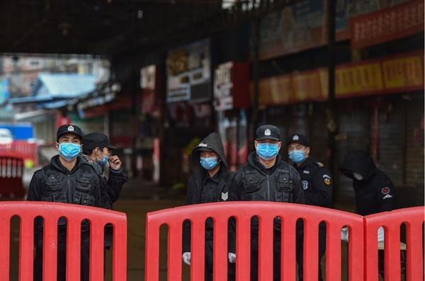 Cảnh sát và nhân viên bảo vệ túc trực bên ngoài chợ Hoa Nam, Vũ Hán ngày 24.1. Ảnh: AFP.