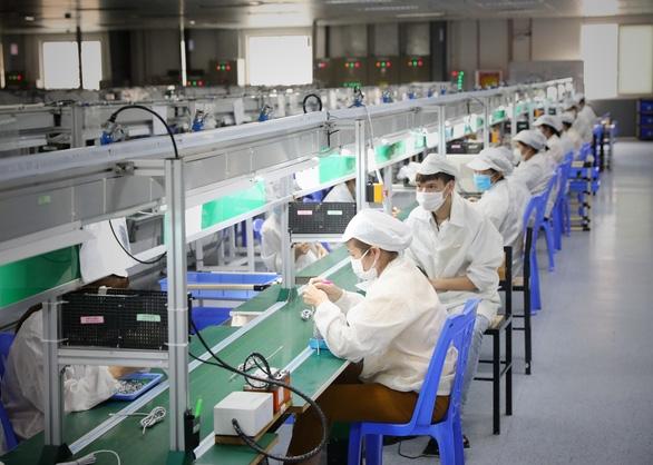 Sáng 29.5, hơn 1.000 công nhân Công ty TNHH New Wing Interconnect Technology (KCN Vân Trung) đã đi làm trở lại sau 2 lần test âm tính với COVID-19. Ảnh: TTXVN.