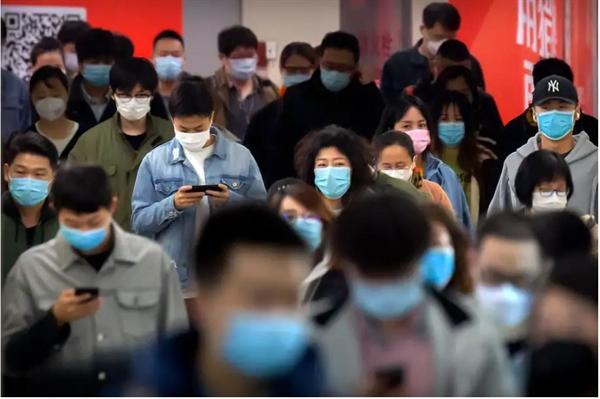 Người đi làm đeo khẩu trang để bảo vệ chống lại sự lây lan của COVID-19 khi họ đi bộ qua một ga tàu điện ngầm ở Bắc Kinh vào tháng 4.2020. Ảnh: AP.