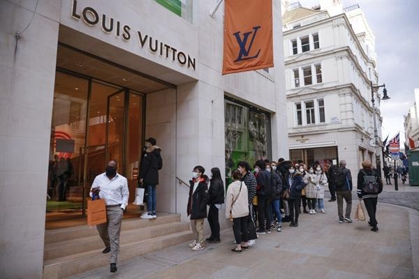 Người mua sắm xếp hàng bên ngoài một cửa hàng Louis Vuitton ở London vào ngày 12.4 khi các cửa hàng không thiết yếu mở cửa trở lại sau gần 100 ngày đóng cửa. Ảnh: Bloomberg.
