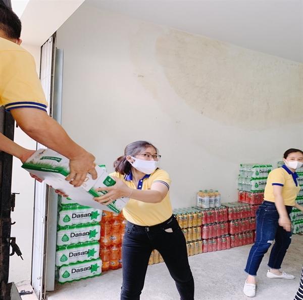 Nhân viên tại PNJ Bắc Ninh vận chuyển hàng hóa lên xe để hỗ trợ người dân đang đang kẹt lại tại nơi tâm dịch.