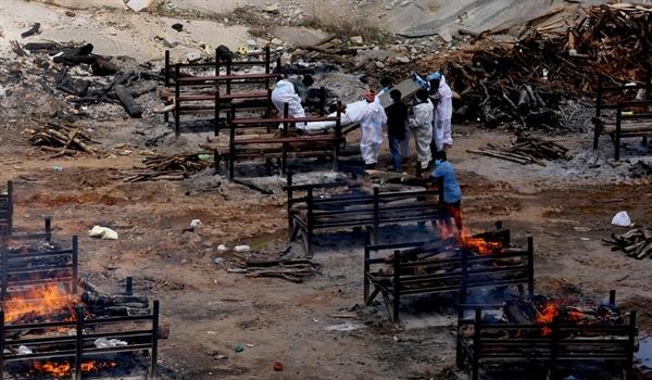 Những giàn hỏa táng nạn nhân COVID-19 bốc cháy trong một đám tang tập thể ở ngoại ô Bangalore, Ấn Độ. Ảnh: EPA.