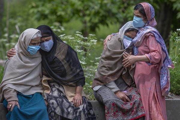 Những người phụ nữ an ủi các thành viên trong gia đình của một nạn nhân COVID-19 tại Srinagar, Ấn Độ. AP.