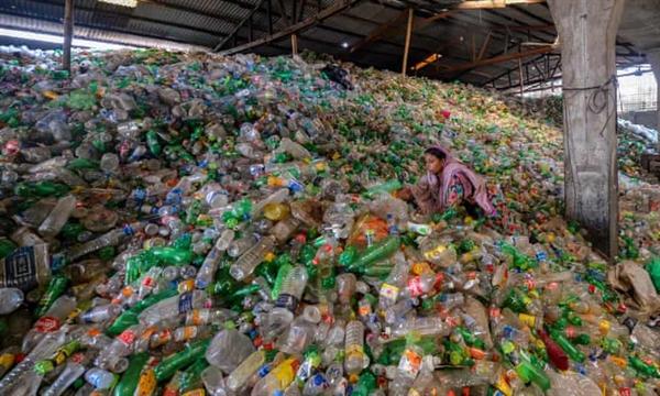 Một công nhân phân loại chai nhựa đã qua sử dụng trong nhà máy tái chế ở Dhaka, Bangladesh. Ảnh: AFP.