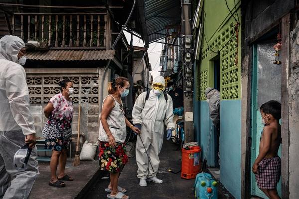 Nhân viên y tế đến phun khử trùng một nhà dân ở Bangkok, Thái Lan vào tháng 5. Ảnh: The New York Times.