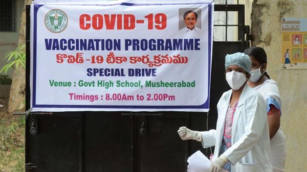 Một bác sĩ đi ngang qua biểu ngữ thông báo về một đợt tiêm chủng COVID-19 ở Hyderabad, Ấn Độ vào ngày 28.5.2021. Ảnh: AFP.