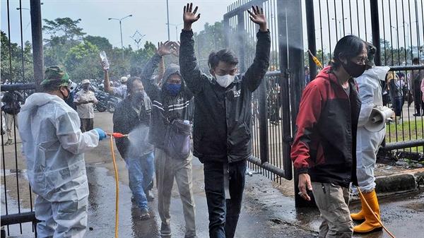 Các binh sĩ Indonesia mặc đồ bảo hộ phun khử trùng vào dòng người tới sân vận động Gelora Bandung Lautan Api ở tỉnh Tây Java, Indonesia. Ảnh: AP.