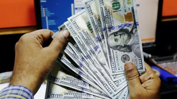 Một thương nhân trưng bày các tờ USD tại một quầy thu đổi ngoại tệ. Ảnh: Reuters.