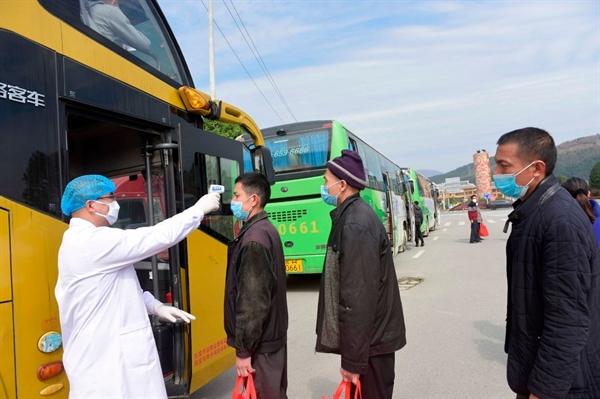 Công nhân nhập cư được kiểm tra nhiệt độ trước khi lên xe buýt để trở về quê. Ảnh: AFP.