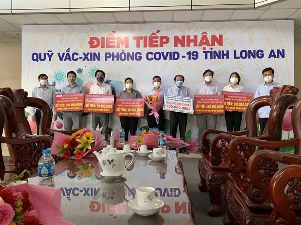 Đại diện Công ty CP Khai thác và Quản lý KCN Đặng Huỳnh (cầm bảng biểu trưng màu trắng) cùng các doanh nghiệp tham gia ủng hộ phòng chống Covid-19 trên địa bàn tỉnh Long An, cam kết sẽ tiếp tục đồng hành cùng các chương trình vì cộng đồng tại địa phương