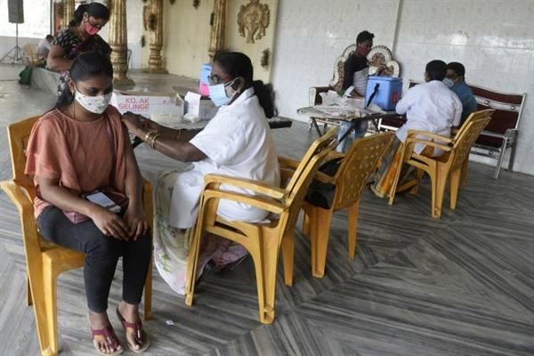 Một nhân viên y tế tiêm vaccine COVID-19 cho một phụ nữ ở ngoại ô Hyderabad, Ấn Độ. Ảnh: AFP.