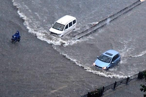 Xe cộ vượt qua dòng nước lũ ở Trịnh Châu thuộc tỉnh Hà Nam, miền Trung Trung Quốc vào ngày 20.7.2021. Ảnh: AP.