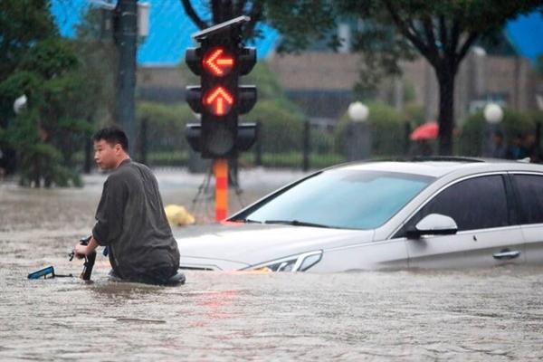 Một người đàn ông đi xe đạp qua một ngã tư ngập lụt ở Trịnh Châu ngày 20.7.2021. Ảnh: AP.