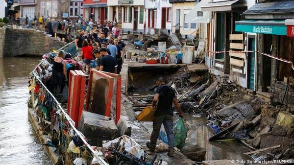 Các nhân viên cảnh sát và tình nguyện viên dọn dẹp đống đổ nát trong khu vực bị ảnh hưởng bởi lũ lụt. Ảnh: Reuters.