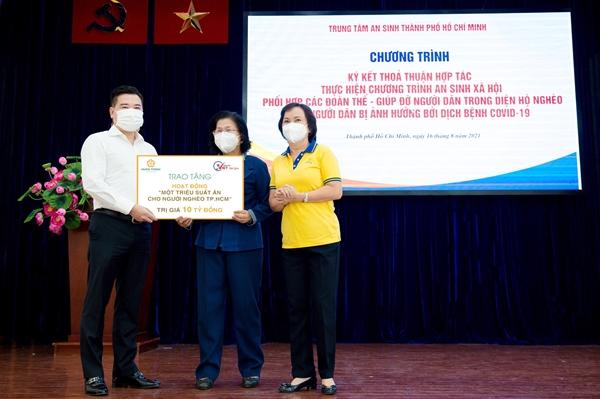 Ông Nguyễn Đình Trung trao biểu trưng 10 tỉ đồng cho bà Vũ Kim Hạnh - Chủ tịch Hội Doanh nghiệp Hàng Việt Nam chất lượng cao, đại diện ban tổ chức chương trình