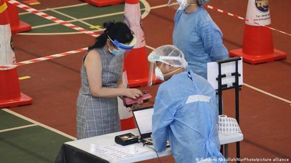 Người dân đăng ký xét nghiệm tại một trung tâm kiểm tra COVID-19 ở Singapore. Ảnh: Deutsche Welle.