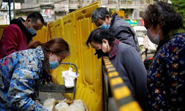 Người dân nhận đồ ăn tại một khu phố bị phong tỏa ở Vũ Hán, tỉnh Hồ Bắc, Trung Quốc, hồi tháng 4/2020. Ảnh: Reuters.