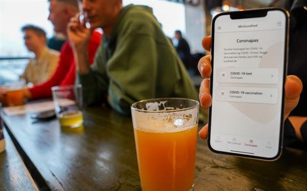 Một người xuất trình coronapas tại quán bar ở Copenhagen. Ảnh: AFP.