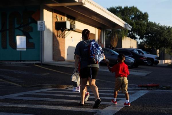 Một phụ huynh dắt con đi học trong ngày đầu tiên đi học, giữa đại dịch COVID-19, tại trường tiểu học West Tampa ở Tampa, Florida, Mỹ, ngày 10 tháng 8 năm 2021. Ảnh: Reuters.